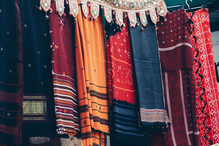 Multi colored flags hanging in a row for sale at market stall