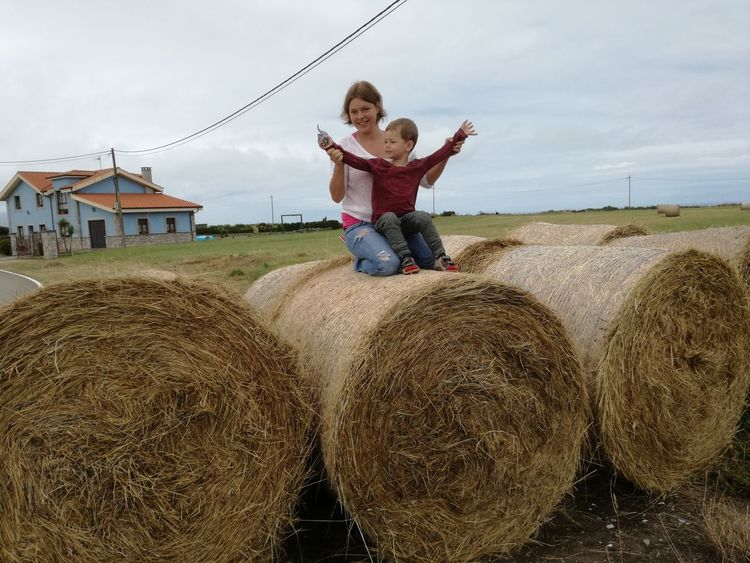 Agriculture Architecture Bale  Day Field Front View Full Length Happiness Hay Hay Bale Haystack Leisure Activity Lifestyles Nature Outdoors People Portrait Real People Rural Scene Sky Smiling Straw Togetherness Young Adult Young Women