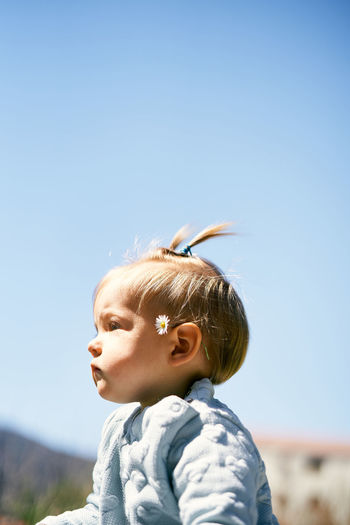Side view of cute baby girl sitting against sky