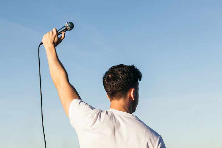 Low angle view of man holding camera against sky