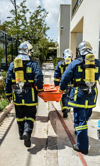 Accidents And Disasters Building Exterior Built Structure Courage Danger Day Firefighter Full Length Headwear Helmet Men Occupation Outdoors Protection Protective Suit Protective Workwear Real People Rear View Rescue Responsibility Safety Service Standing Uniform Work Helmet