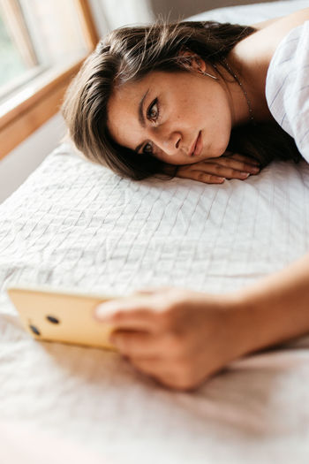 Side view of young woman using mobile phone while lying on bed at home
