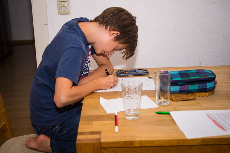 Side view of boy writing at home