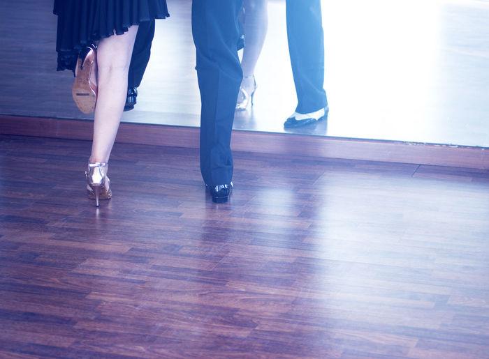 Low section of women standing on hardwood floor
