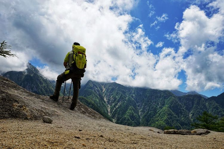 Rear view of man hiking on mountains