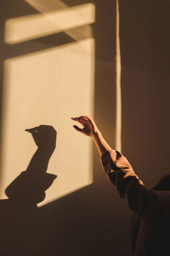 Cropped hand of woman gesturing against wall