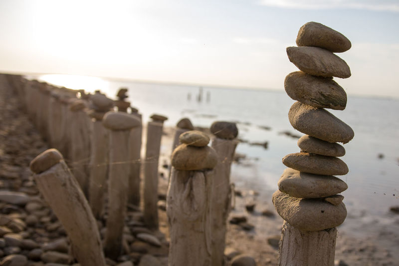 Close-up of wooden posts on sea against sky