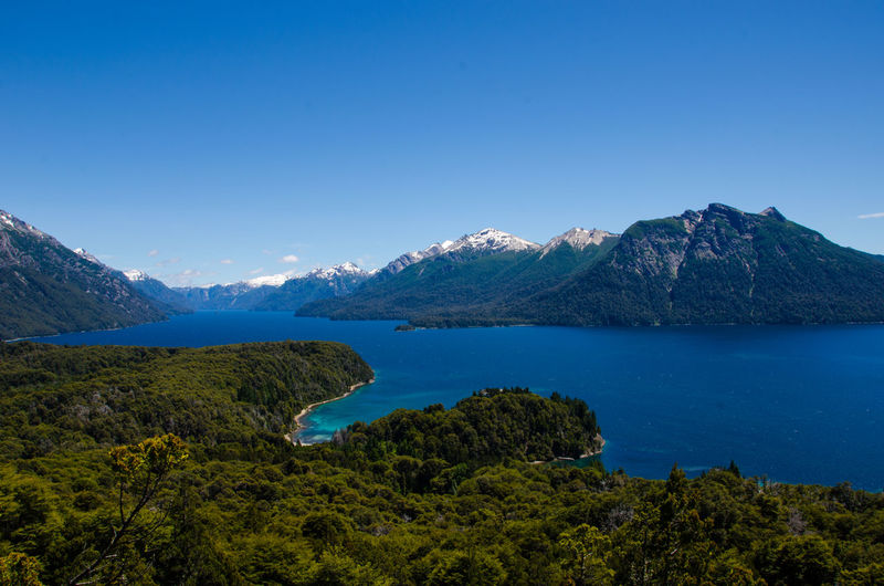 Scenic view of mountains and lake against clear blue sky