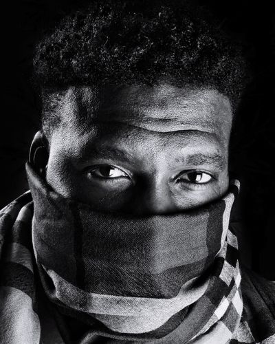 Close-up portrait of man covering face with scarf against black background