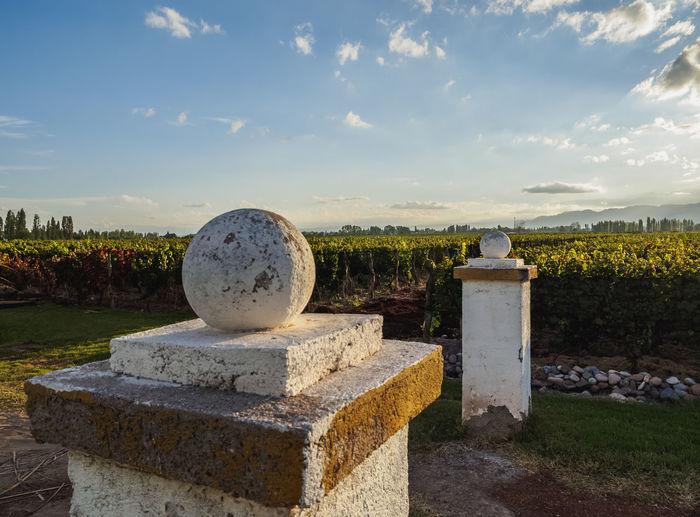 Stone cross in cemetery against sky