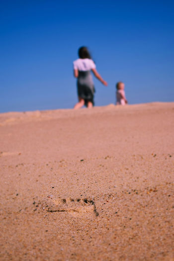 Rear view of woman with daughter walking on sand at beach