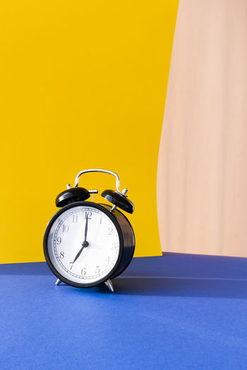 Close-up of clock on table against yellow background