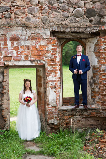 Bride and groom standing at abandoned wall