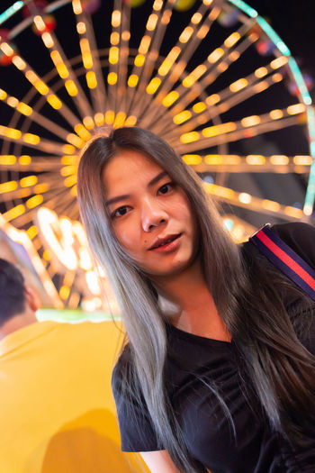 Portrait of smiling young woman in amusement park at night