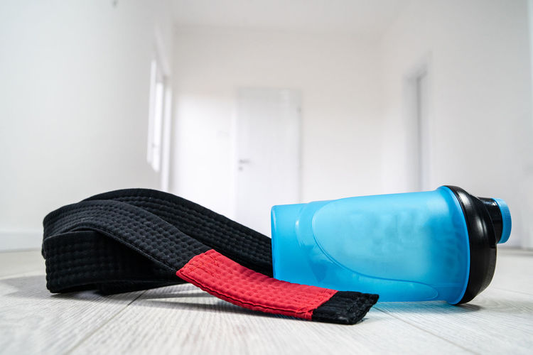 Indoors  Still Life Flooring No People Focus On Foreground Close-up Blue Black Color Wall - Building Feature Home Interior Shoe Table Personal Accessory Red Absence Single Object Sports Equipment Sport Wood