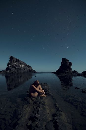 Side View Of Naked Woman Hugging Self At Rocky Shore