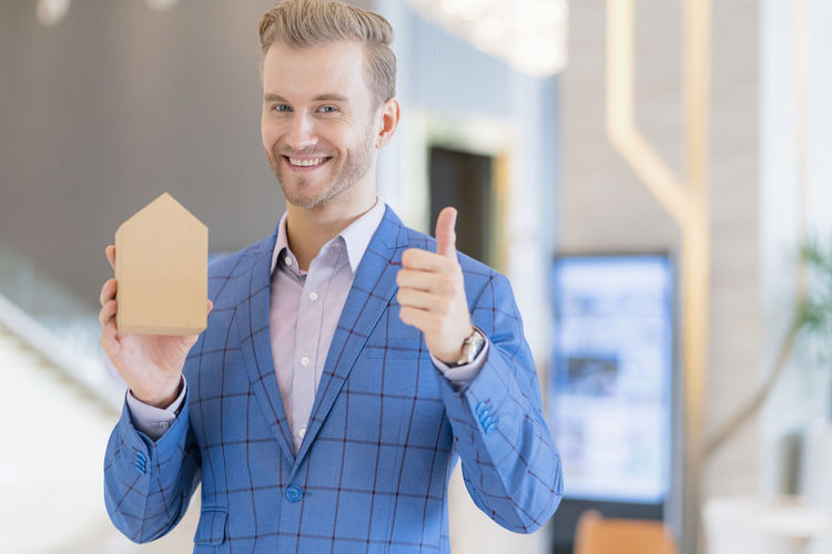Portrait of smiling businessman showing thumbs up sign while holding model house