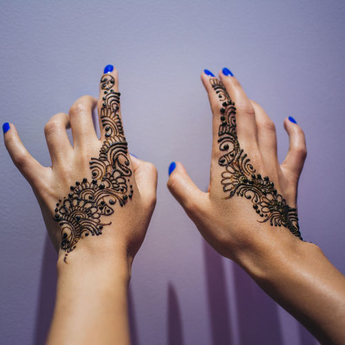 Cropped Hands Of Woman With Henna Tattoo By Wall