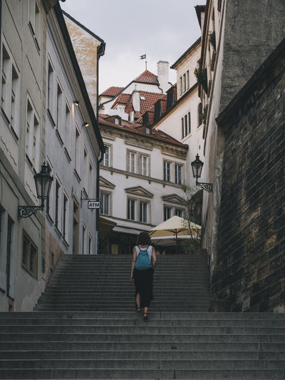 Rear view of woman walking on street amidst buildings in city