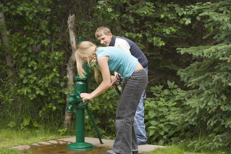 Siblings using hand pump against plants