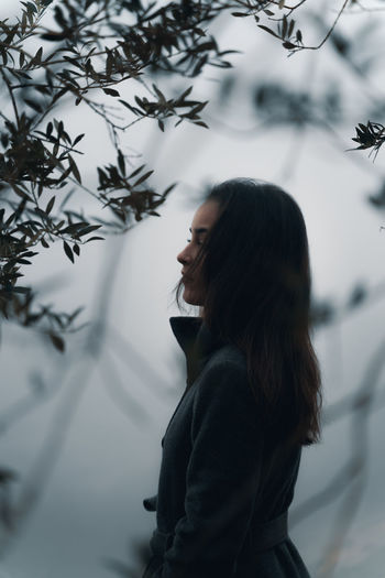 Side view of woman between trees against fog
