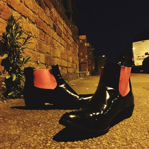 Pair of orange and black patent leather shoes lit by street lights Shoes Black And Orange Color Patent Leather Night ShotoniPhone6s Square Discarded Boots Street Photography Fashion Rubbish Photos