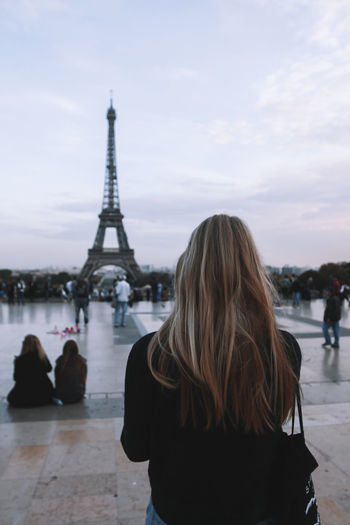Rear View Of Woman Standing Against Eiffel Tower