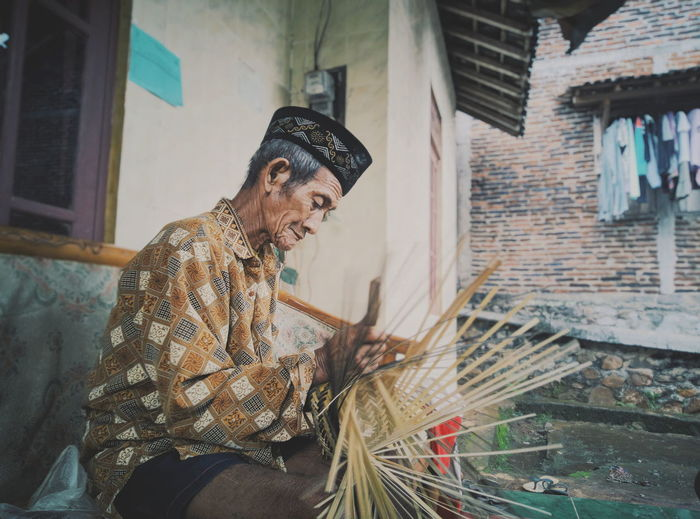 Side View Of Man Making Wicker Basket Outside House