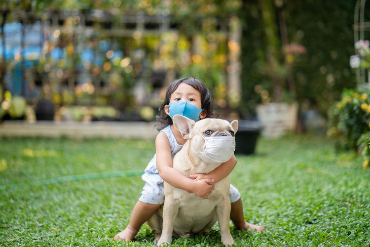 Full length of girl with dog on grassy land
