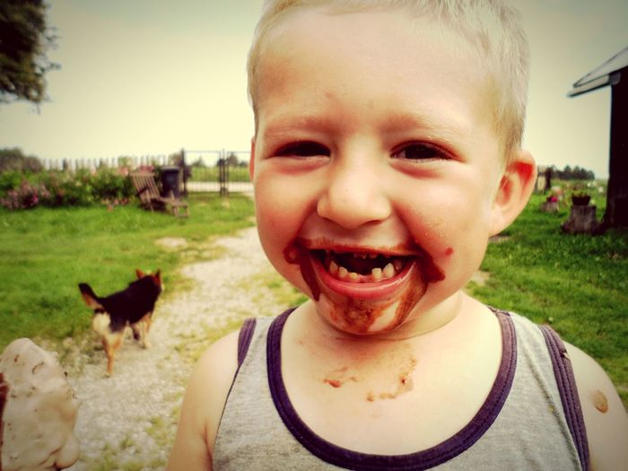 Portrait Of Cute Boy Laughing With Chocolate On His Face