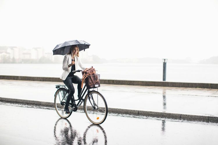 Man riding bicycle on wet road against sky during rainy season