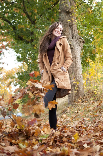 Low angle view of woman kicking fallen autumn leaves at park