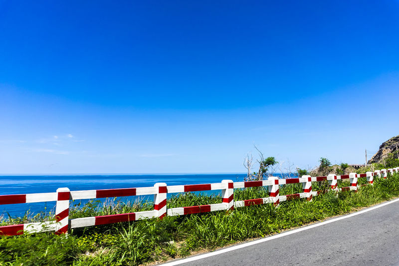 Empty road by sea against blue sky
