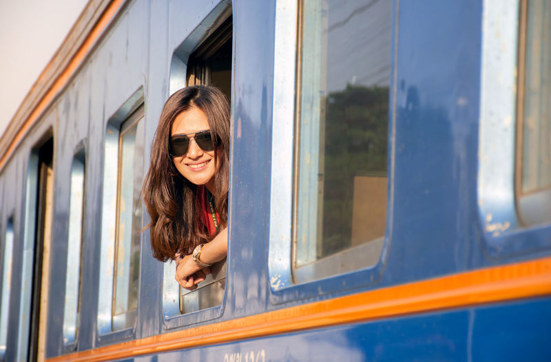 Portrait of smiling woman looking through window of train