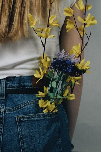 Midsection of woman with flowers in back pocket