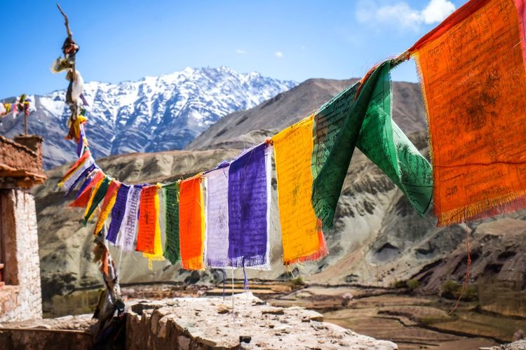 Multi colored flags hanging on mountain against sky