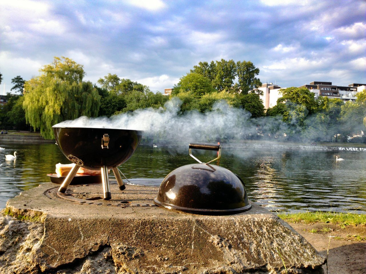 Close-up of barbecue against calm lake