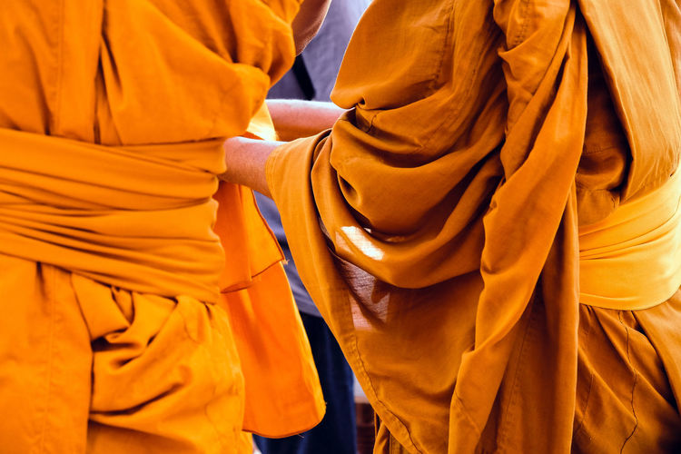 Midsection of monks wearing traditional clothing while standing outdoors