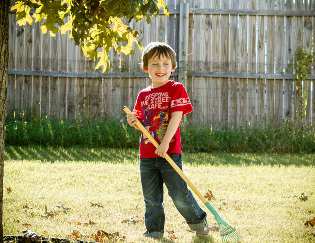 Full length of boy with gardening rake at yard