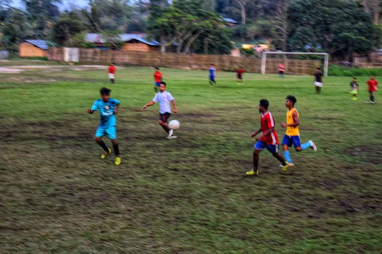 Group of people running on soccer field