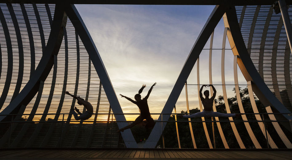 Woman with men dancing on footbridge against sky at sunset