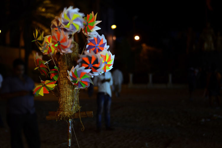 Pinwheels for sale on road at night