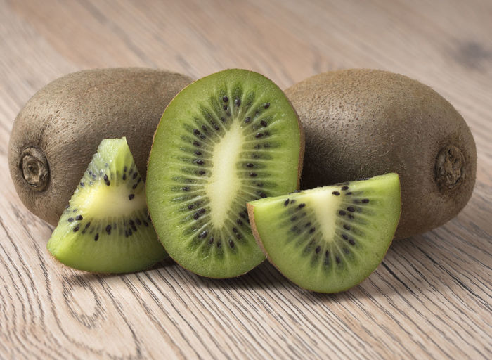 Ripe juicy kiwi fruit with sliced segments on wooden background. Fruit, Kiwi, Food, Ingredient, Juicy, Green, Nutrition, Half, Vitamin, Fresh, Sweet, Healthy, Diet, Ripe, Slice, Background, Brown, Vegetarian, Tropical, Cut, Tasty, Natural, Snack, Color, Raw, Nature, Seed, Health, Section, Closeup, Freshness, Table, Nob Healthy Eating Food Fruit Food And Drink Wellbeing Freshness Kiwi Still Life Wood - Material No People Indoors  Close-up Cross Section SLICE Kiwi - Fruit Green Color Group Of Objects Table Three Objects Focus On Foreground