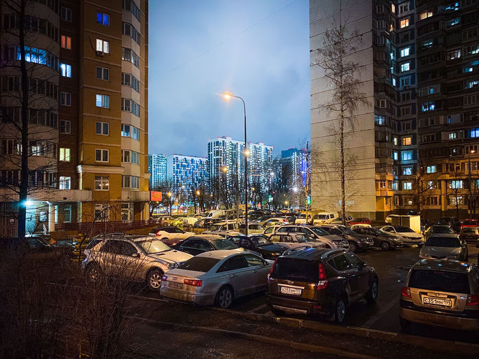 Cars on city street by buildings against sky at night