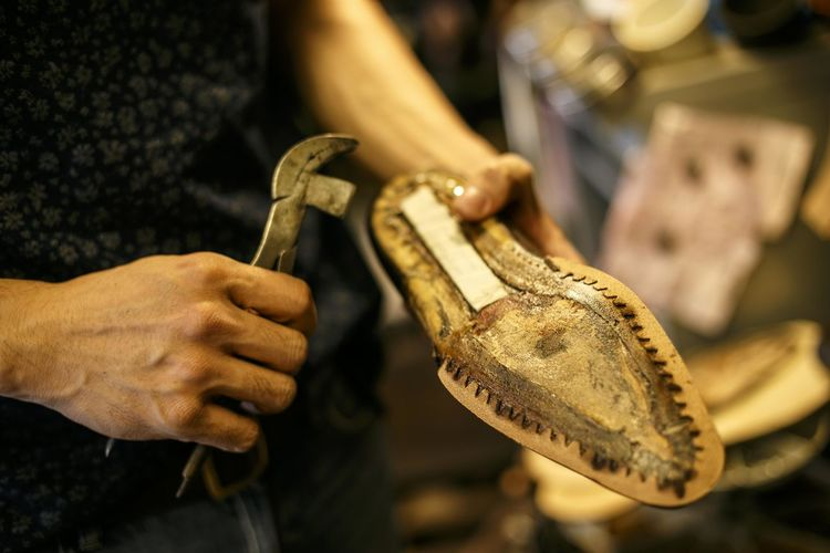 Midsection of shoemaker holding sole of shoe