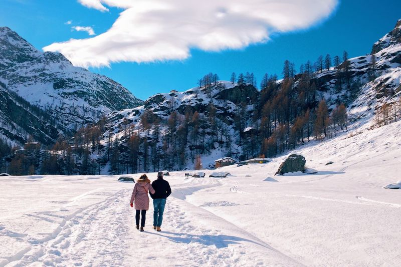 Rear view of two people walking on snow covered mountain