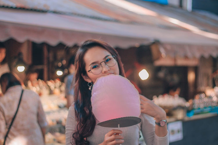 Portrait of woman holding cotton candy at market