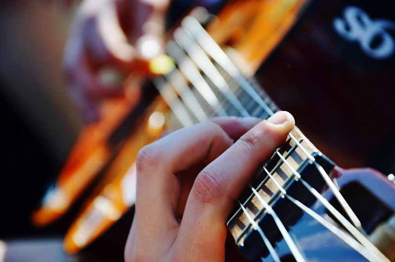 Cropped hands playing guitar