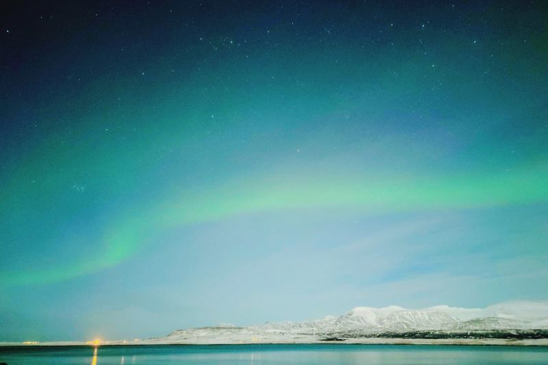 Scenic view of sea against northern lights in sky at night
