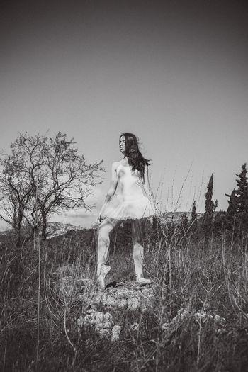 Full length of girl standing on field against clear sky